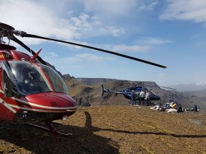 Helicopter and people enjoying the sun on a mountaintop in the highlands